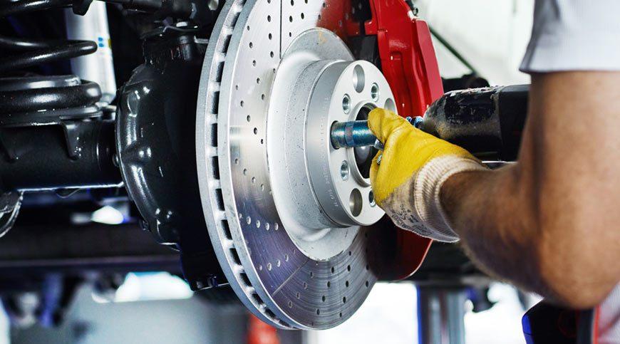 A car mechanic in a garage repairs a brake