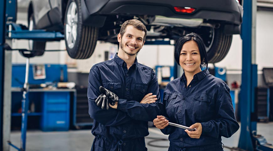 Two happy mechanics - man and woman standing by the car